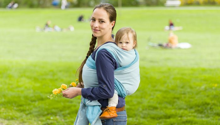 59239832 - a young mother carrying her little baby in a sling on her back and walked in beautiful sunny weather by a park. the two laugh and have fun